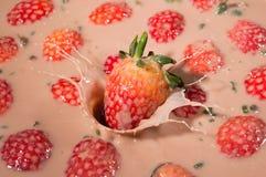 Erdbeeren, die in den Jogurt fallen Stockbild
