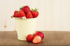 Erdbeeren in einem Eimer auf Holztisch Lizenzfreie Stockbilder