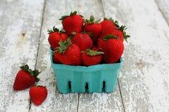 Erdbeeren in einem Grünbuchkarton auf weißem Holz stockfotos
