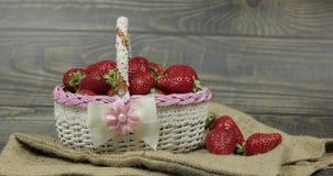 Erdbeeren in einem kleinen Korb auf dem Holztisch - nah oben stock video