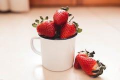 Erdbeeren in einem weißen Emailbecher stockbilder