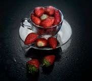 Erdbeeren in einer Glasschale auf schwarzem Glas Lizenzfreie Stockfotografie