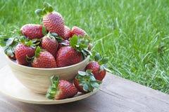 Erdbeeren in einer hölzernen Schüssel auf einem grünen Hintergrund Lizenzfreies Stockfoto