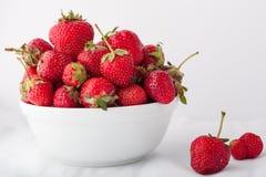 Erdbeeren in einer weißen Schüssel auf einem weißen Hintergrund Lizenzfreie Stockfotografie