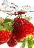 Erdbeeren fielen in ein Glas Sodawasser Lizenzfreie Stockbilder