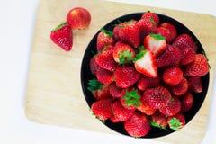 Erdbeeren frisch in einer schwarzen Schale auf einer hölzernen Platte mit einem Whit Lizenzfreie Stockfotografie