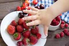 Erdbeeren, Himbeeren, Kirschen auf Tabelle child& x27; s-Handreichweite Lizenzfreie Stockbilder