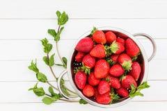 Erdbeeren im rustikalen Sieb und in der Minze auf weißem Holztisch Stockfotos