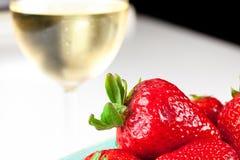 Erdbeeren mit Glas weißem Wein Stockbilder