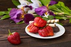 Erdbeeren mit Schokolade auf einem Hintergrund von Blumen Hölzerne Tabelle Nahaufnahme lizenzfreie stockfotos