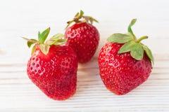 Erdbeeren reif auf einem weißen hölzernen Hintergrund Lizenzfreies Stockbild
