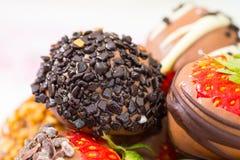 Erdbeeren tauchten in Schokolade mit Nüssen auf einer Tabelle ein Abschluss oben Lizenzfreies Stockbild