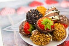 Erdbeeren tauchten in Schokolade mit Nüssen auf einer Tabelle ein Abschluss oben Stockbilder