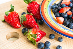 Erdbeeren und Blaubeeren auf dem hölzernen Brett Stockfoto