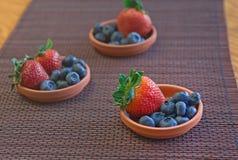 Erdbeeren und Blaubeeren in den kleinen Lehmtellern auf einer Matte Stockfotografie