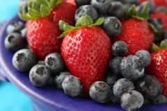 Erdbeeren und Blaubeeren in der blauen Schüssel Lizenzfreie Stockfotografie