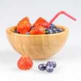 Erdbeeren und Blaubeeren in der hölzernen Schale Stockbilder