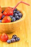 Erdbeeren und Blaubeeren in der hölzernen Schale mit Stroh Stockfotografie