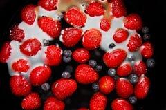 Erdbeeren und Blaubeeren im Wasser Lizenzfreie Stockbilder