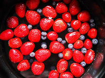 Erdbeeren und Blaubeeren im Wasser Lizenzfreies Stockfoto