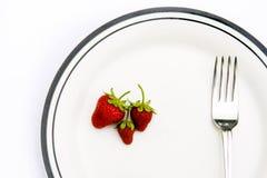 Erdbeeren und Gabel auf einer Platte Stockbild