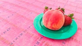 Erdbeeren und Pfirsich in einer Platte Stockbilder