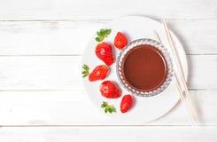 Erdbeeren und Schokoladencreme auf weißem hölzernem Hintergrund Stockfotografie