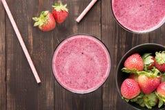 Erdbeeresmoothie und frische Erdbeeren im Glas auf hölzernem Ba Stockbilder