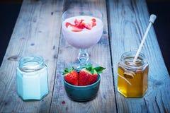 Erdbeeresmoothiebestandteile: neue strwawberries in einer Schüssel, in einem Honig und in einem Jogurt in den Gläsern Stockbilder