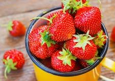 Erdbeergarten-rustikaler Schalen-Sommer-Lebensmittel-gelbes Metallhintergrund-selektiver Fokus stockbilder