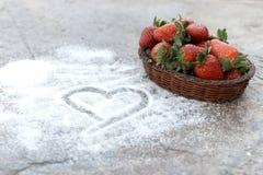 Erdbeerkorb auf Zuckerhintergrund mit einem Herzen gezeichnet auf es stockbilder