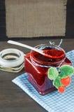 Erdbeermarmelade in einem Glas auf hölzernem Hintergrund Stockfotografie