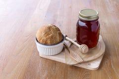 Erdbeermarmelade im Glas und im frischen selbst gemachten Brot auf hölzernem backgroun Stockfotografie
