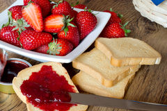 Erdbeermarmelade mit Zwieback auf Holztisch Stockfotos