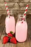 Erdbeermilch in den Flaschen auf Holz Stockbilder