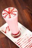 Erdbeermilchshake im hohen Glas auf Holztisch stockfotografie
