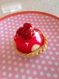 Erdbeertörtchen auf rosa pickeliger Platte Stockfotografie