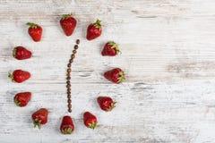 Erdbeeruhr mit den Pfeilen von Kaffeebohnen, zwölf Stunden dreißig Minuten auf einer hölzernen antiken Tabelle in der Küche zeige Stockfotografie