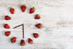 Erdbeeruhr mit Pfeilen von den Kaffeebohnen, der Zeit bei acht O-` Uhr dreißig Minuten oder zwanzig Stunden an zeigend dreißig Mi Lizenzfreie Stockfotos