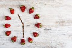 Erdbeeruhr mit Pfeilen von den Kaffeebohnen, der Zeit bei elf O-` Uhr dreißig Minuten oder dreiundzwanzig Stunden dreißig Minute  Lizenzfreies Stockfoto