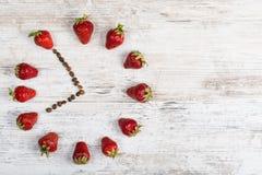 Erdbeeruhr mit Pfeilen von den Kaffeebohnen, der Zeit von sieben Stunden fünfundfünfzig Minuten zeigend oder von neunzehn Stunden Lizenzfreie Stockbilder