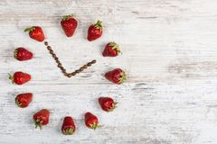 Erdbeeruhr mit Pfeilen von den Kaffeebohnen, die der Zeit dreizehn Stunden fünfundfünfzig Minuten oder eine Stunde fünfundfünfzig Stockbild