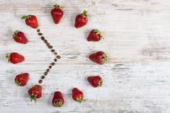 Erdbeeruhr mit Pfeilen von den Kaffeebohnen, die eine Zeit von sechs oder achtzehn Stunden fünfundfünfzig Minuten auf einem alten Lizenzfreie Stockbilder