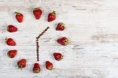 Erdbeeruhr mit Pfeilen von den Kaffeebohnen, die einer Zeit von einer Stunde dreißig Minuten oder dreizehn Stunden dreißig Minute Stockbilder