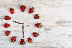 Erdbeeruhr mit Pfeilen von den Kaffeebohnen, die neun Stunden dreißig Minuten oder zwanzig eine Stunde dreißig-Minute-hölzerne An Stockfotos