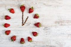 Erdbeeruhr mit Pfeilen von den Kaffeebohnen, die Zeit in einer Stunde oder in dreizehn Stunden auf einem hölzernen alten Hintergr lizenzfreie stockfotos