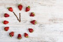 Erdbeeruhr mit Pfeilen von den Kaffeebohnen, welche die Zeit von elf oder dreiundzwanzig Stunden fünfundfünfzig Minuten auf einem Stockbild
