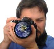 Erde im Kameraobjektiv, schießendes Foto Stockfotografie