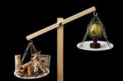 Erde und Geld auf zwei Pan Balance Stockbild