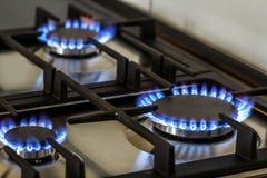 Erdgas, das auf Küchengasherd in der Dunkelheit brennt Platte vom Stahl mit einem Gaskocherbrenner auf einem schwarzen Hintergrun lizenzfreies stockbild